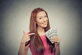 Closeup portrait super happy excited successful young business woman holding money dollar bills in hand isolated grey wall background. Positive emotion facial expression feeling. Financial reward.jpeg